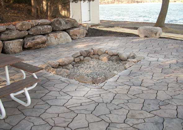 Inset stone fireplace inside lakeside patio