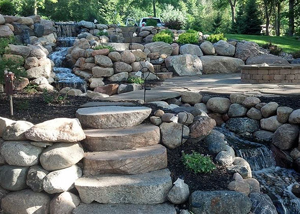 Boulder garden with large stone steps and flowing waterfall